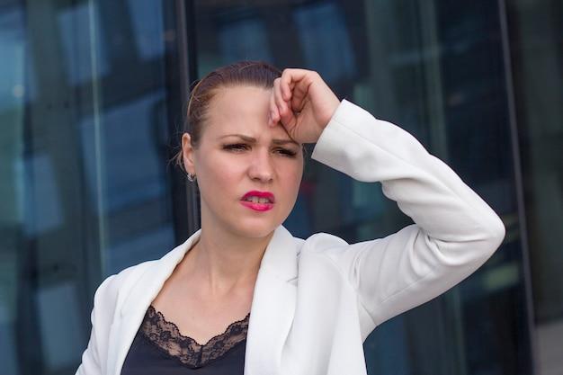 Cansado exausta jovem empresária sofrendo de dor de cabeça, desesperada e estressada porque dor e enxaqueca ao ar livre. mão na cabeça. trabalho estressante difícil, trabalho, tendo problemas. sentindo doente.