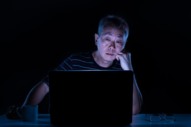 Cansado homem asiático de meia idade, trabalhando em seu computador em seu escritório em casa à noite
