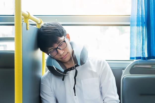 Cansado homem confortavelmente em ônibus e dormir com travesseiro inflável cervical pescoço, transporte