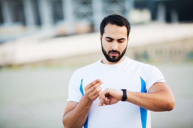 Cansado homem corredor resto depois de correr na cidade stree