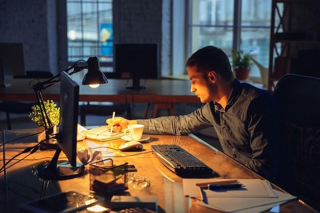 Cansado. homem trabalhando sozinho no escritório, ficando até tarde da noite.
