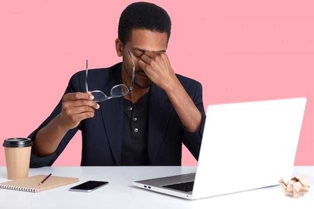 Cansado jovem afro-americano usando laptop enquanto está sentado na mesa branca, vestindo jaqueta preta, esfrega os olhos, tem dor nos olhos depois de muito trabalho no computador portátil, homem trabalhador ganha dinheiro online.