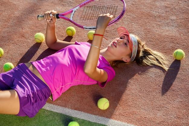 Cansado jovem tenista em uniforme rosa encontra-se na quadra de tênis com muitas bolas e jogando com raquete de tênis. vista do topo.