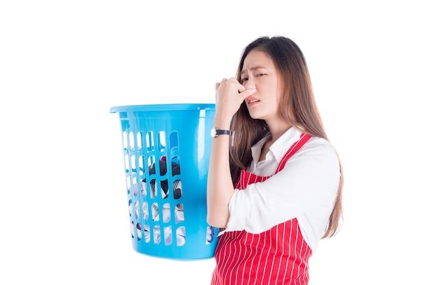 Cansado linda mulher asiática usando avental vermelho e segurando a cesta de roupas