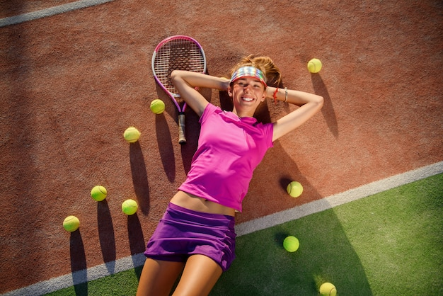 Cansado, mas sorridente jovem tenista em uniforme rosa encontra-se na quadra de tênis ao ar livre com muitas bolas após treinamento duro ao pôr do sol. vista do topo.