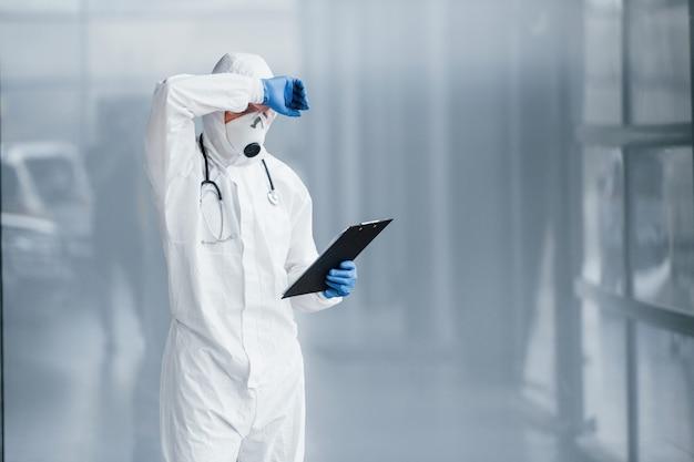 Cansado médico cientista no jaleco, óculos defensivos e máscara faz uma pausa