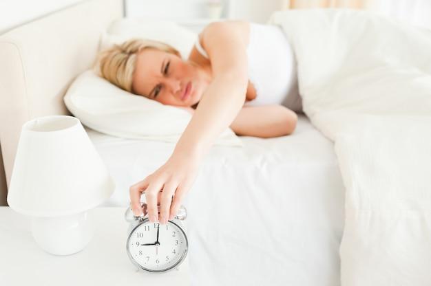 Cansado mulher desligar o despertador
