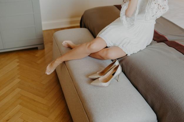 Cansado mulher irreconhecível em vestido branco, tira sapatos de salto alto enquanto chega em casa