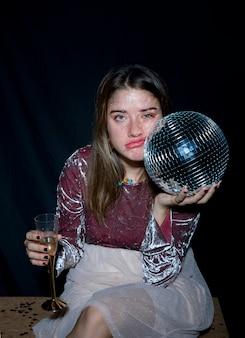 Cansado mulher sentada com bola de discoteca na mão