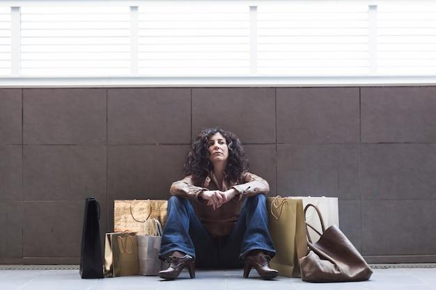 Cansado mulher sentada com sacos de compras na rua