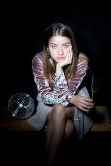 Cansado mulher sentada com taça de champanhe na mão