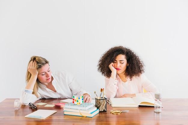 Cansado mulheres sentadas à mesa
