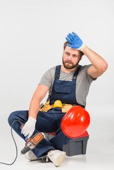 Cansado reparador sentado com broca na caixa de ferramentas