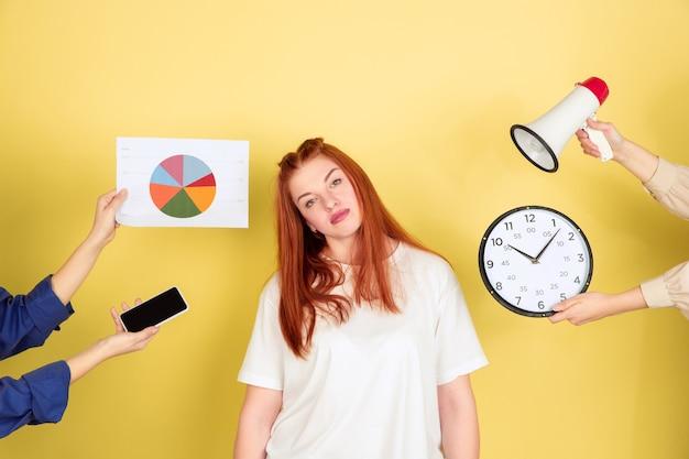 Cansado. retrato de mulher jovem caucasiana em fundo amarelo do estúdio, muitas tarefas. como gerenciar o tempo certo. conceito de trabalho de escritório, negócios, finanças, freelance, autogestão, planejamento.