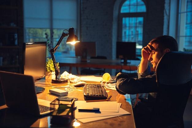 Cansado, triste. homem trabalhando sozinho no escritório durante a quarentena do coronavírus ou covid-19, permanecendo até tarde da noite. jovem empresário, gerente fazendo tarefas com smartphone, laptop, tablet no espaço de trabalho vazio.