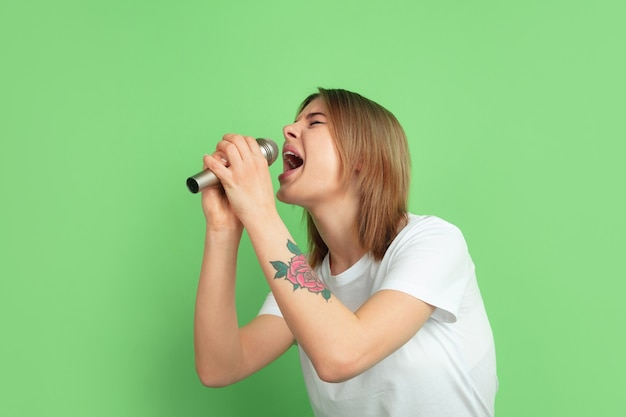 Cantando com alto-falante. retrato de mulher jovem branca isolado na parede verde do estúdio