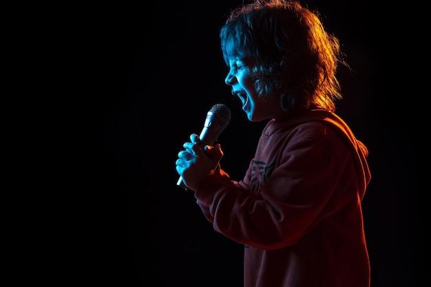 Cantando como celebridade, rockstar. retrato do menino caucasiano em fundo escuro do estúdio em luz de néon. lindo modelo cacheado.