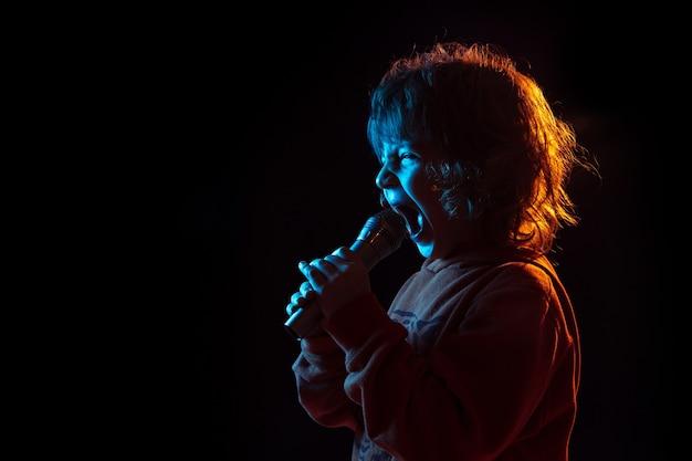 Cantando como celebridade, rockstar. retrato do menino caucasiano na parede escura em luz de néon. lindo modelo cacheado. conceito de emoções humanas, expressão facial, vendas, anúncio, música, hobby, sonho.