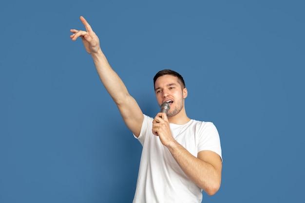 Cantando como celebridades, estrelas. retrato de jovem caucasiano sobre fundo azul.