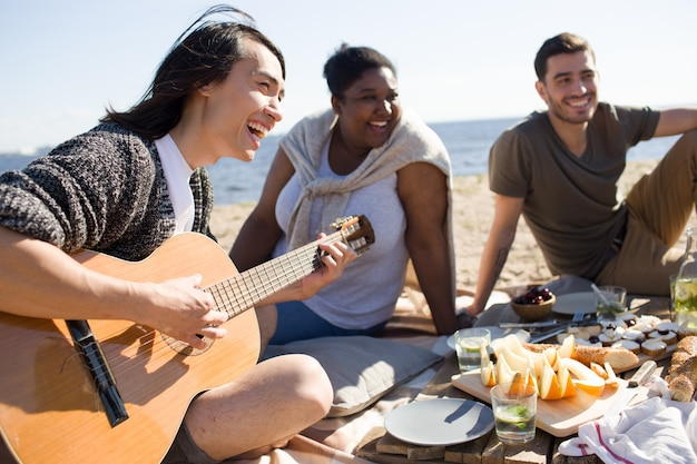 Cantando e tocando guitarra em um piquenique