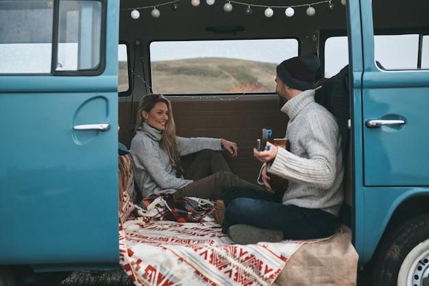Cantando uma canção de viagem. jovem bonito tocando violão para sua linda namorada enquanto está sentado em uma mini van azul estilo retro
