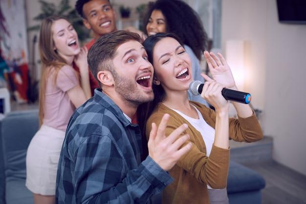 Cantar dueto jovem casal animado ou amigos segurando um microfone e cantando juntos enquanto tocam