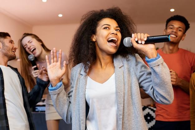 Cante em uma garota de raça mista e parecendo feliz segurando o microfone e cantando em uma festa de karaokê