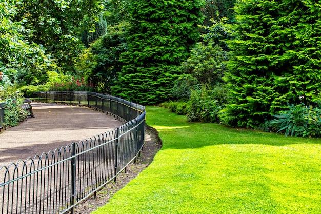 Canteiro de flores e grama atrás da cerca no parque de londres