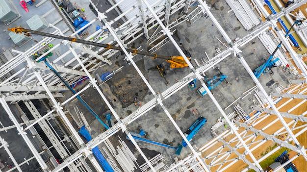 Canteiro de obras aéreo da vista superior com construção de maquinaria industrial para construções novas da fábrica.