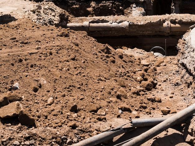 Canteiro de obras com canos velhos escavados