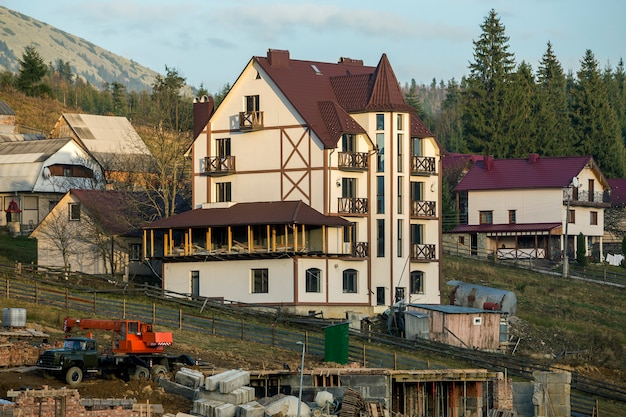 Canteiro de obras com guindaste de construção e casa de hotel confortável moderno novo com telhado shingled na área rural ecológica em árvores spruce e colinas de montanhas sob o céu azul.
