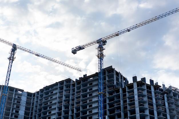 Canteiro de obras com guindaste de construção e céu nublado no fundo
