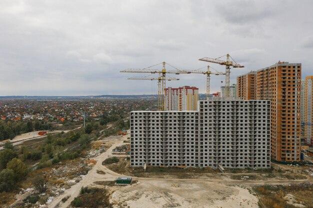 Canteiro de obras com guindastes construção de novo edifício alto