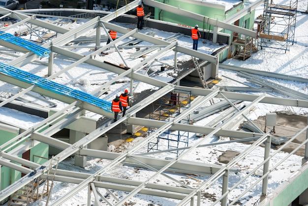 Canteiro de obras com trabalhadores no telhado do prédio