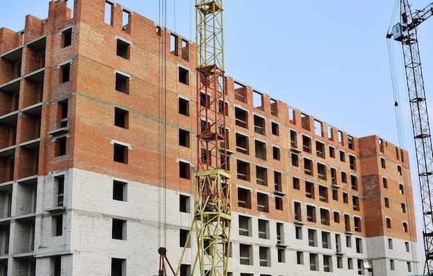 Canteiro de obras de casa de tijolos com guindaste e construção.