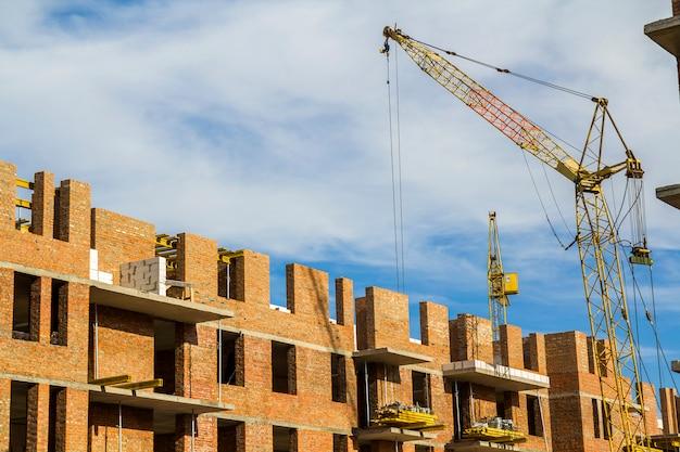 Canteiro de obras de um prédio alto do novo apartamento com guindastes de torre contra o céu azul. desenvolvimento de área residencial. conceito de crescimento de projeto imobiliário.