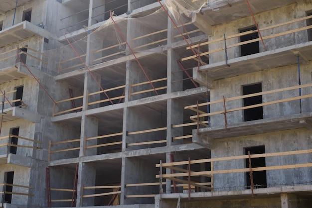 Canteiro de obras, fora. close-up de um prédio de apartamentos em construção. paredes e andaimes de concreto, fachada.