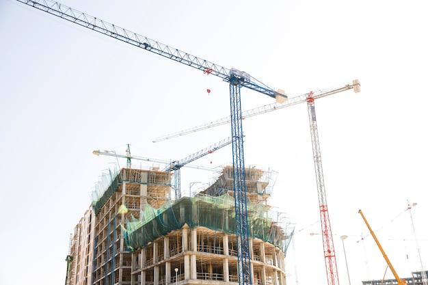 Canteiro de obras incluindo vários guindastes trabalhando em um complexo de edifícios