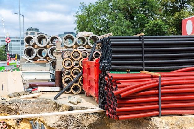Canteiro de obras, materiais de construção, velha cidade europeia. engenharia urbana, tubos de plástico e concreto, europa