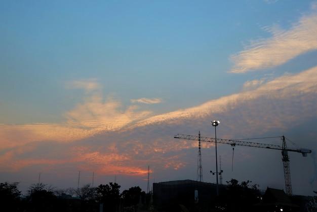 Canteiro de obras mostrado em silhueta contra o céu colorido da noite com céu azul e nuvens. industrial.