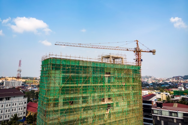 Canteiro de obras próximo a um edifício residencial moderno. guindaste de trabalho e rede de segurança com céu azul de nuvem. a grade verde evita que objetos caiam de altura. antecedentes industriais