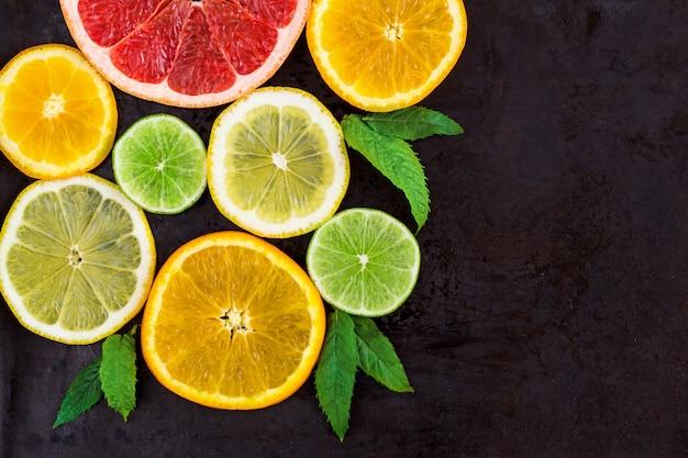 Canto com fatia de laranjas, limões, limas, toranja e hortelã padrão em preto