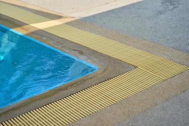 Canto da piscina com grelha de drenagem de água com sombra