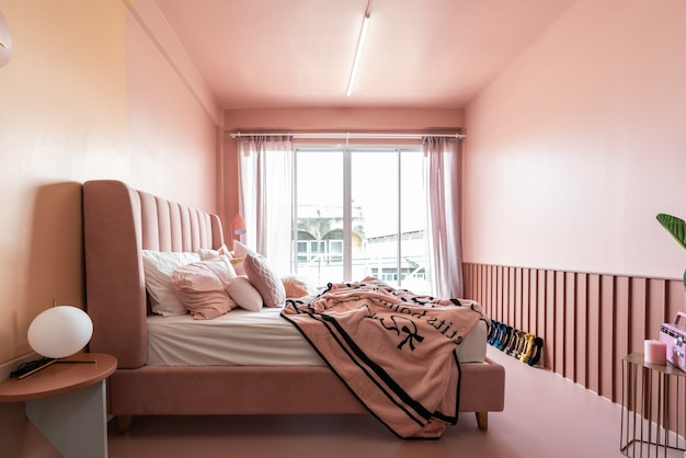 Canto de quarto aconchegante rosa com cama de tecido de veludo rosa bebê decorada por cobertor, travesseiros e luminária de chão rosa com parede pintada de rosa em dois tons