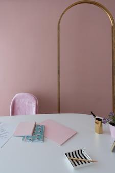 Canto de trabalho aconchegante rosa com moldura em arco de ouro antigo e parte superior branca com cadernos rosa, listras de cerâmica e flores em vaso