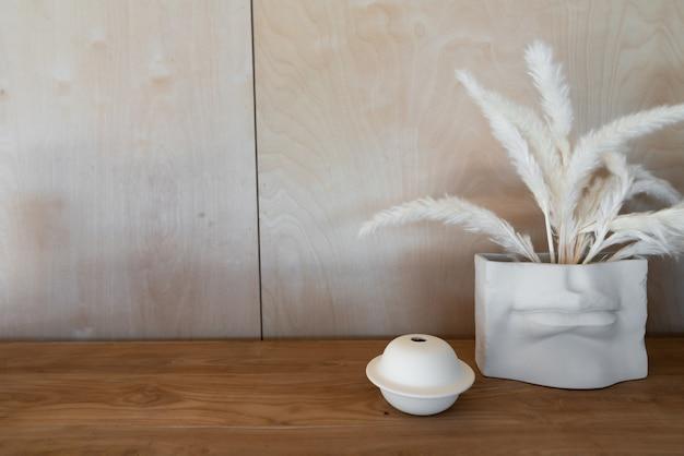 Canto de trabalho decorado com planta artificial dentro de vaso em tampo de madeira situado em ambiente de luz natural / espaço de cópia do interior do apartamento