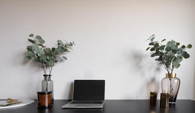 Canto de trabalho do quarto com laptop, velas brancas e planta artificial na mesa de trabalho de madeira preta.