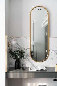 Canto de trabalho do quarto decorado com espelho de ouro inoxidável e planta artificial em vaso de vidro na mesa de trabalho cinza pintada com spray com parede de mármore