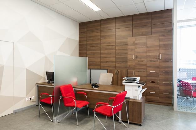 Canto do escritório moderno, com paredes brancas e de madeira, piso cinza, área de espaço aberto com poltronas vermelhas e brancas e quartos atrás da parede de vidro