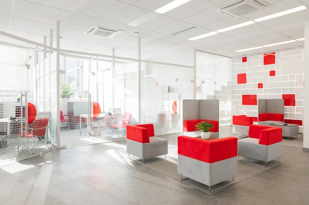 Canto do escritório moderno, com paredes brancas, piso cinza, área de espaço aberto com poltronas vermelhas e brancas e quartos atrás da parede de vidro